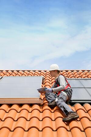 Man on roof solar energy installation