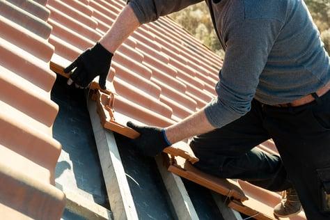 Worker installs roof tiles in Las Vegas on roof of home