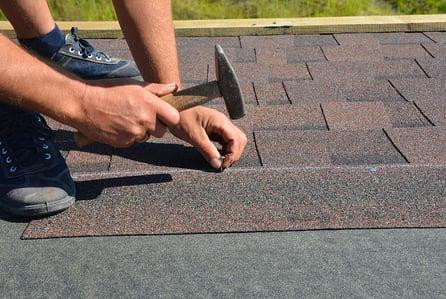 Roof installer performing roof shingles repair on roof of Las Vegas home